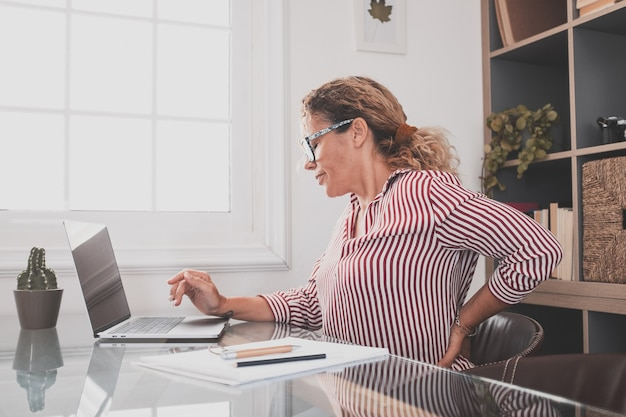 Nahaufnahme der rückansicht gestresste junge frau, die den unteren rücken berührt, sich unwohl fühlt, unter plötzlichen schmerzen aufgrund von sitzender lebensweise oder langer computerüberlastung in falscher haltung im home office leidet.