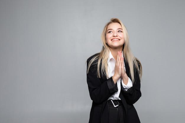 Nahaufnahme der ruhigen jungen geschäftsfrau, die hände zusammen im beten setzt. geschäfts- und gebetskonzept