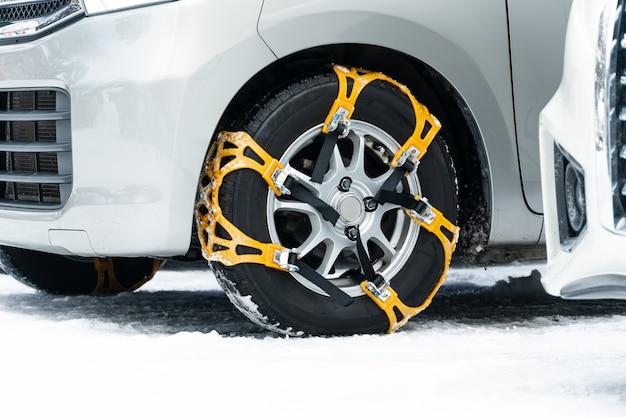 Nahaufnahme der rutschfesten radkette der gelben ketten. die reifen von fahrzeugen sind so montiert, dass sie beim fahren durch schnee und eis maximale traktion bieten.