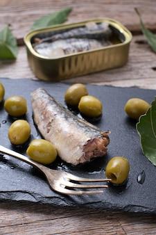 Nahaufnahme der sardine in dosen auf schwarzem stein und oliven