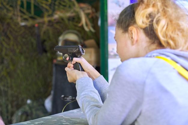 Nahaufnahme der schießpistole des teenager-mädchenschießens am schießstand.