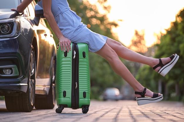 Nahaufnahme der schlanken beine der jungen frau, die auf koffertasche neben auto stillstehen. reise- und urlaubskonzept.