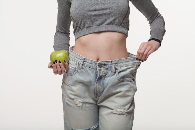 Nahaufnahme der schlanken taille der jungen frau in den großen jeans, die erfolgreichen gewichtsverlust zeigen