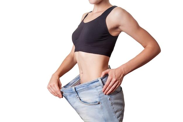 Nahaufnahme der schlanken taille der jungen frau in großen jeans mit erfolgreichem gewichtsverlust, isoliert auf weißem hintergrund, diätkonzept.