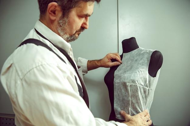 Nahaufnahme der schneidertabelle mit den männlichen händen, die stoffherstellungsmuster für kleidung im traditionellen atelierstudio verfolgen. der mann im frauenberuf. konzept der gleichstellung der geschlechter