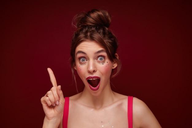 Nahaufnahme der schockierten jungen hübschen braunhaarigen frau mit lässiger frisur, die zeigefinger erhebt und mit großen augen und geöffnetem mund schaut, isoliert