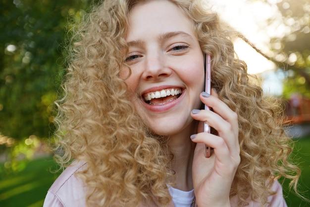 Nahaufnahme der schönen blonden frau, die mit jemandem am telefon spricht, breit lächelnd