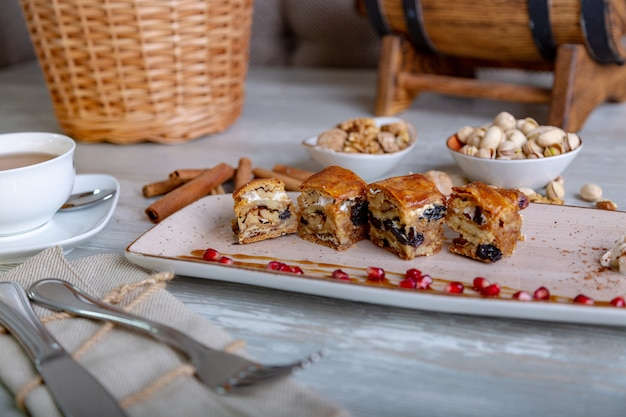 Nahaufnahme der schönen eleganten östlichen süßigkeiten, baklava, serviert auf dem teller. schöne dekoration, restaurantgericht, essfertig. teezeit, gemütliche atmosphäre.