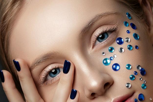 Nahaufnahme der schönen frau, die ihr gesicht berührt. perfektes haut- und mode-make-up.