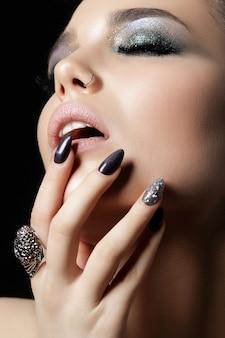 Nahaufnahme der schönen frau, die ihre lippen berührt. perfekte haut und abend make-up