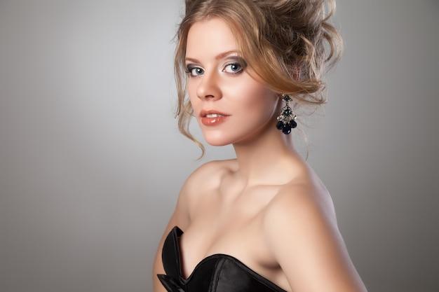 Nahaufnahme der schönen frau mit abend-make-up und großen schwarzen ohrringen, die in die kamera schauen. schmuck und schönheit. modefoto