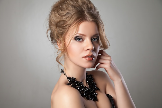 Nahaufnahme der schönen frau mit abend-make-up und großer schwarzer halskette, die ihr gesicht berührt. schmuck und schönheit. modefoto