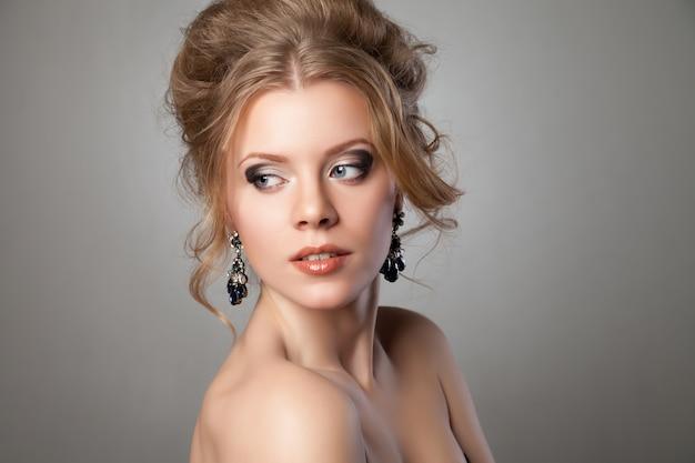 Nahaufnahme der schönen frau mit abendmake-up und großen schwarzen ohrringen. schmuck und schönheit. modefoto
