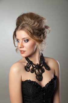 Nahaufnahme der schönen frau mit abendmake-up und großer schwarzer halskette. schmuck und schönheit. modefoto