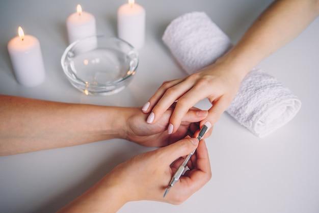 Nahaufnahme der schönen frauenhände, die maniküre im spa-salon draufsicht erhalten.