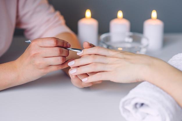 Nahaufnahme der schönen frauenhände, die maniküre im spa-salon erhalten