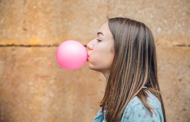 Nahaufnahme der schönen jungen brünetten teenager-mädchen bläst rosa kaugummi über eine steinmauer