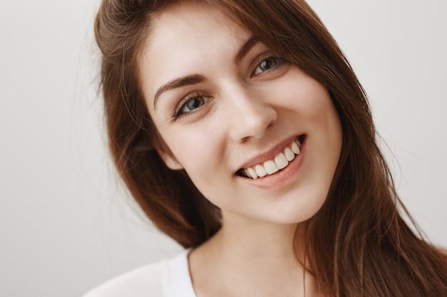 Nahaufnahme der schönen jungen frau, die glücklich schaut und mit weißen zähnen lächelt