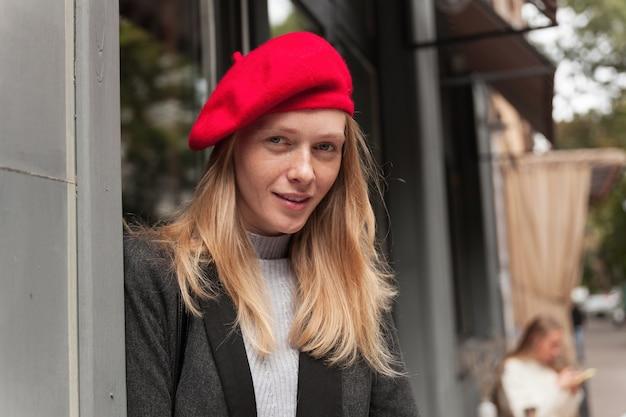 Nahaufnahme der schönen jungen frau mit langen blonden haaren, die elegante kleidung tragen, während sie leicht posiert, schaut und lächelt