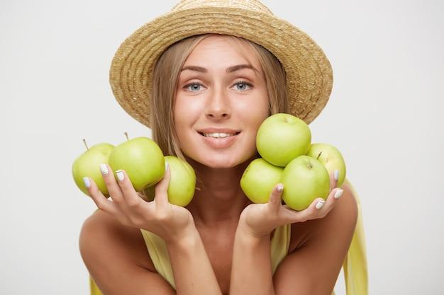 Nahaufnahme der schönen jungen positiven blonden frau mit natürlichem make-up, das grüne äpfel nahe ihrem gesicht hält und kamera mit charmantem lächeln betrachtet, lokalisiert über weißem hintergrund