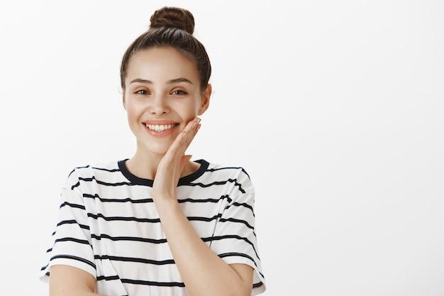 Nahaufnahme der schönen lächelnden frau, die saubere perfekte hautwange, konzept der schönheit und der hautpflege berührt