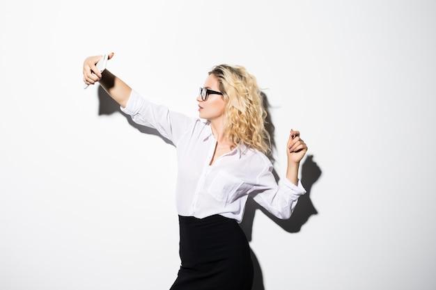 Nahaufnahme der schönen verspielten geschäftsfrau, die selfie foto auf lokalisierter weißer wand macht