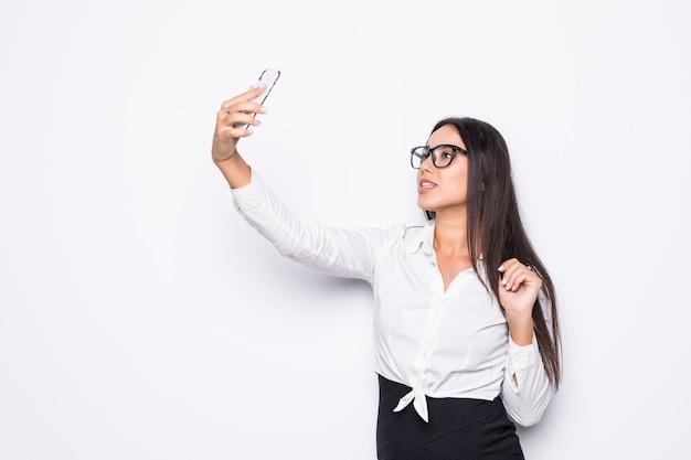 Nahaufnahme der schönen verspielten geschäftsfrau in den augengläsern, die selfie foto auf weiß machen