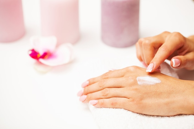 Nahaufnahme der schönen weiblichen hand, die handcreme anwendet.