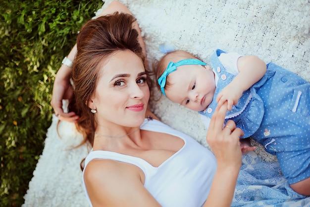 Nahaufnahme der schönheit liegend auf dem gras mit ihrem netten baby im blauen kleid. fürsorgliche mutter mit dem kleinen mädchen, das spaß zusammen im sommerpark hat.