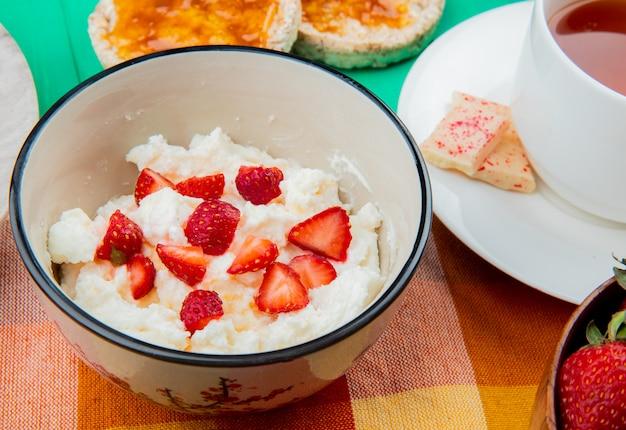 Nahaufnahme der schüssel hüttenkäse mit erdbeer-tasse tee-knäckebrot auf stoff