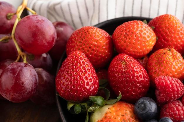 Nahaufnahme der schüssel mit früchten und trauben