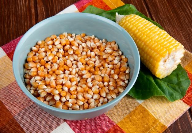 Nahaufnahme der schüssel mit getrocknetem maiskorn und gekochtem mais mit spinat auf kariertem stoff und holzoberfläche