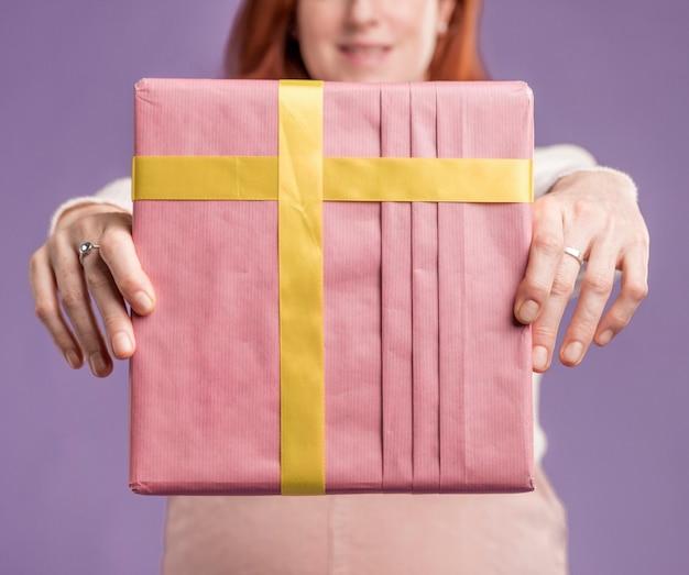 Nahaufnahme der schwangeren frau, die geschenk hält