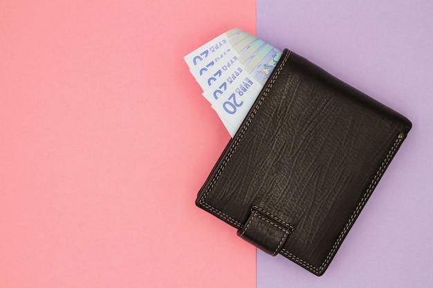 Nahaufnahme der schwarzen brieftasche mit euro-banknoten auf einem farbigen hintergrund