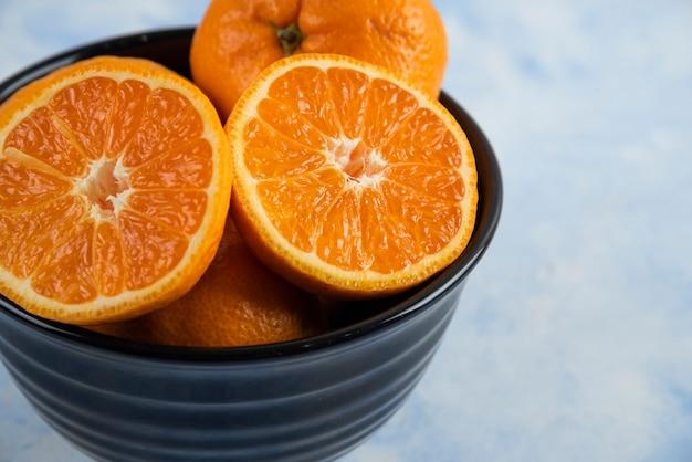 Nahaufnahme der schwarzen schüssel voll mit ganzen oder halb geschnittenen mandarinen