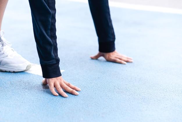 Nahaufnahme der selektiven fokusfrauenhand auf der blauen laufstrecke, die sich zum start bereit macht