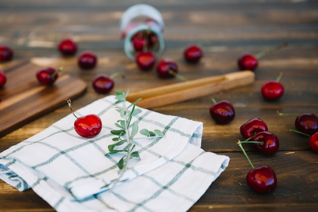 Nahaufnahme der serviette und der zerstreuten roten kirschen auf hölzernem schreibtisch