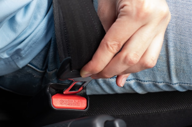 Nahaufnahme der sicherheitsgurtbefestigung eines jungen mannes in einem auto, eine fahrerin legt einen sicherheitsgurt an.