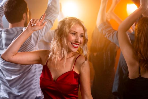 Nahaufnahme der smiley-frau, die im club tanzt