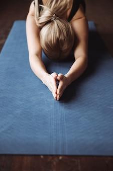 Nahaufnahme der sportlerin, die yoga auf matte praktiziert