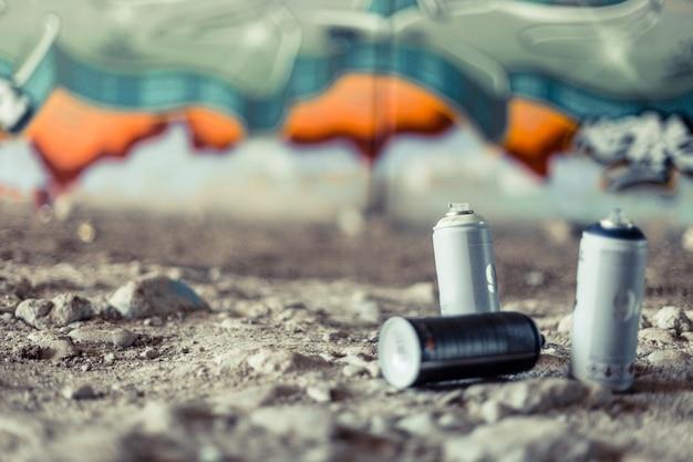Nahaufnahme der spraydosen vor graffitiwand