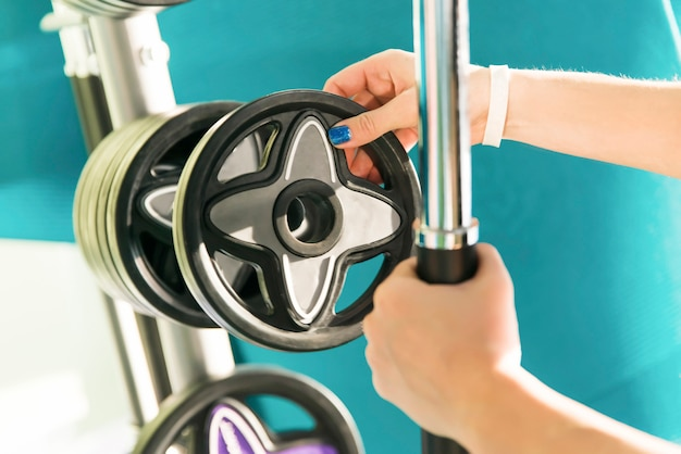 Nahaufnahme der starken frau vorbereitend für trainingstraining und zusätzliche gewichtsplatte für barbell hinzufügend