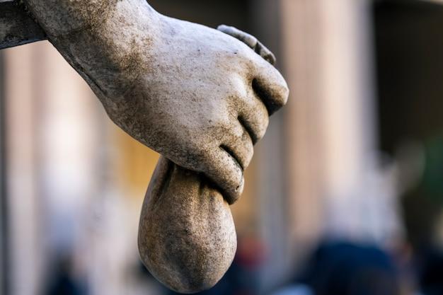 Nahaufnahme der statuenhand mit einer tüte münzen. einsparungskonzept.