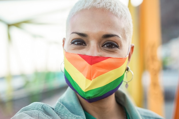 Nahaufnahme der stolzen glücklichen jungen lesbischen frau, die lgbt regenbogenfahne hält - fokus auf gesicht
