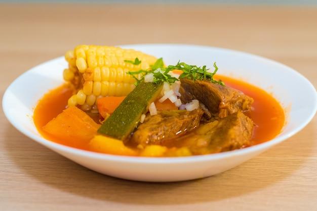 Nahaufnahme der suppe in einer weißen schüssel auf einer holzoberfläche