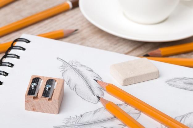 Nahaufnahme der tabelle des künstlers oder des designers. bleistifte, schärfer und radiergummi auf skizzenbuch mit handgezeichneten federn