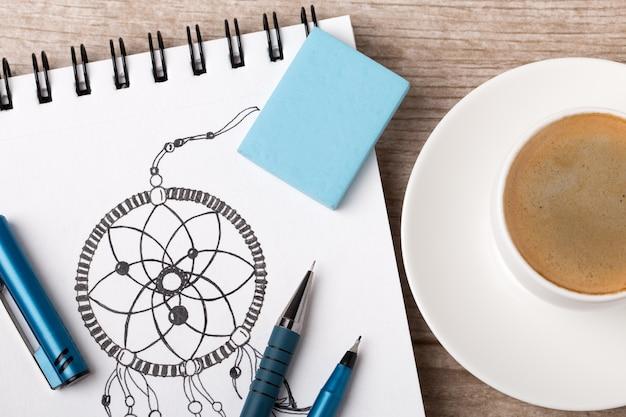 Nahaufnahme der tabelle des künstlers oder des designers. tasse kaffee, bleistift, feiner liner und radiergummi auf skizzenbuch mit handgezeichnetem traumfänger