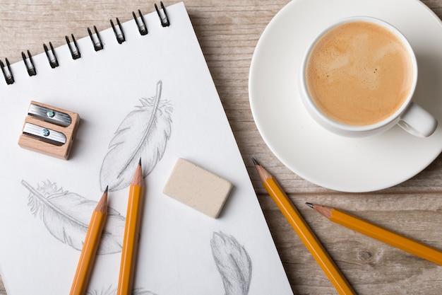 Nahaufnahme der tabelle des künstlers oder des designers. tasse kaffee, bleistifte, schärfer und radiergummi auf skizzenbuch mit handgezeichneten federn