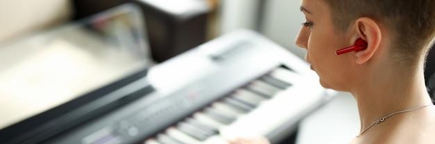 Nahaufnahme der talentierten frau, die auf synthesizer spielt. modernes instrument für musiker. kurzhaarige junge frau, die melodie am klavier durchführt. musik- und hobbykonzept