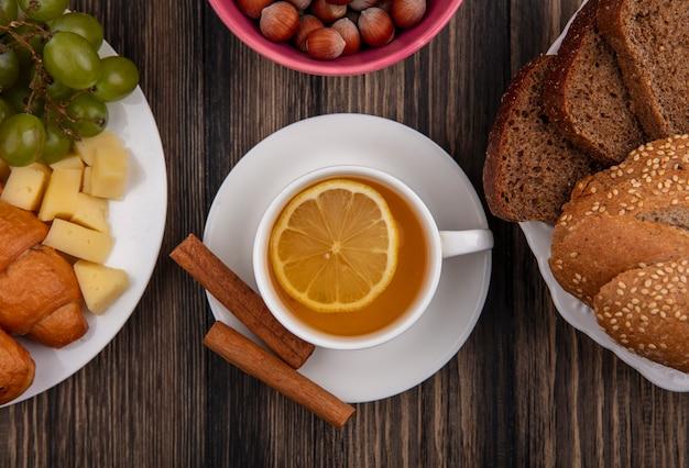 Nahaufnahme der tasse des heißen wirbel mit zimt auf untertasse und nüssen mit käse-trauben-croissant und teller brotscheiben auf holzhintergrund